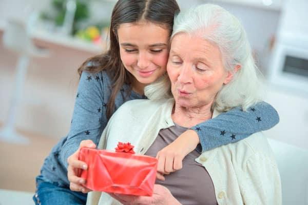 Внучка вручает подарок бабушке