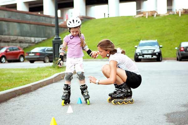 Девочка учится кататься на роликах