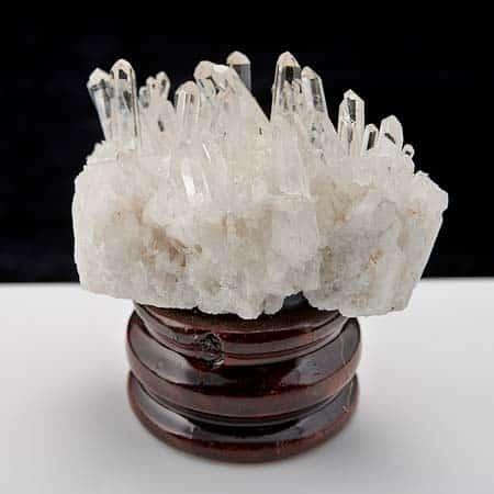 Друза кристаллов горного хрусталя на деревянной подставке