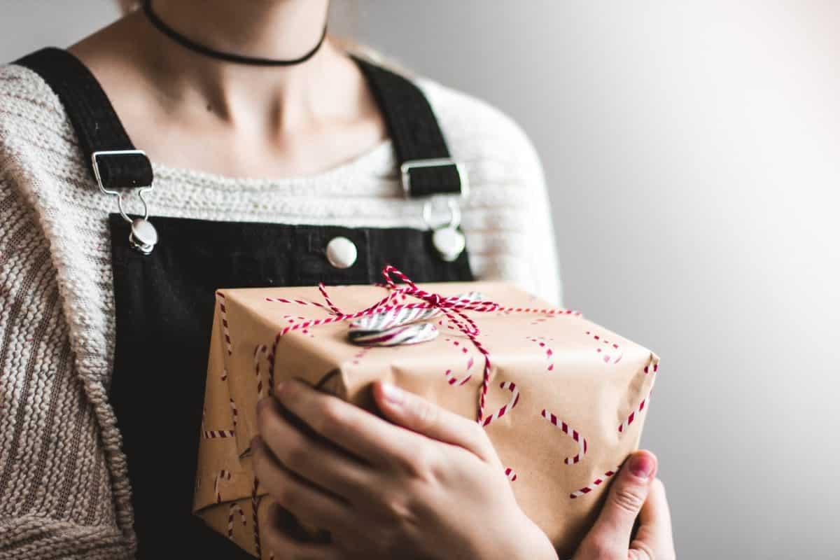 Женщина держит коробку с подарком