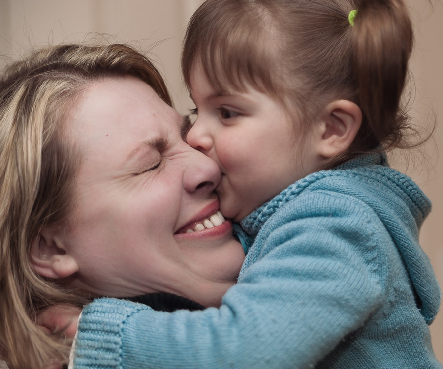 Женщина целует девочку в нос