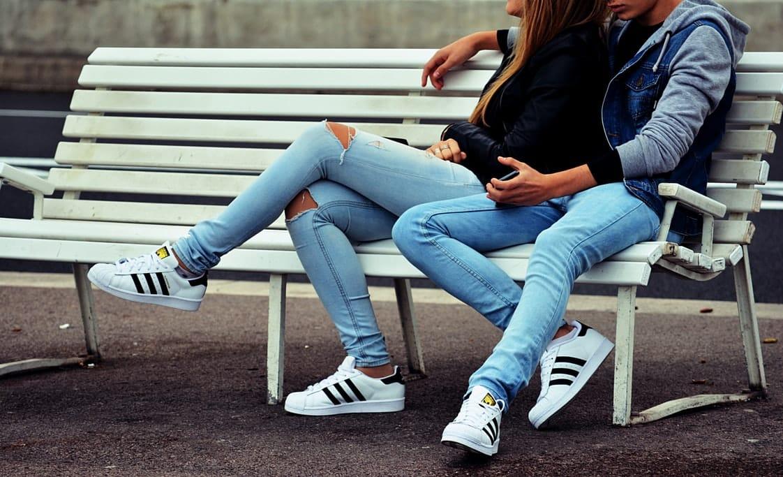 Пара сидит на белой скамейке