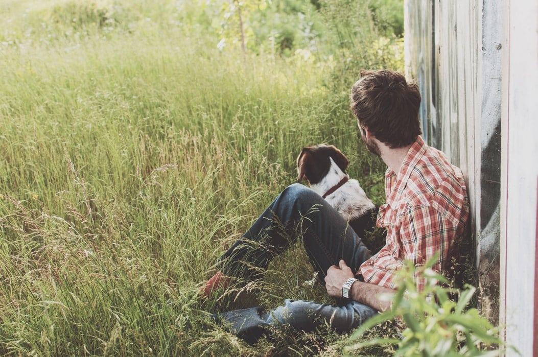 Мужчина сидит на траве с собакой