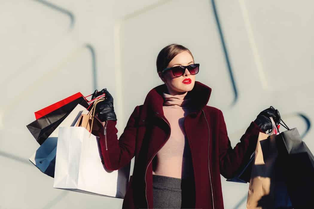 Женщина держит в руках пакеты с покупками