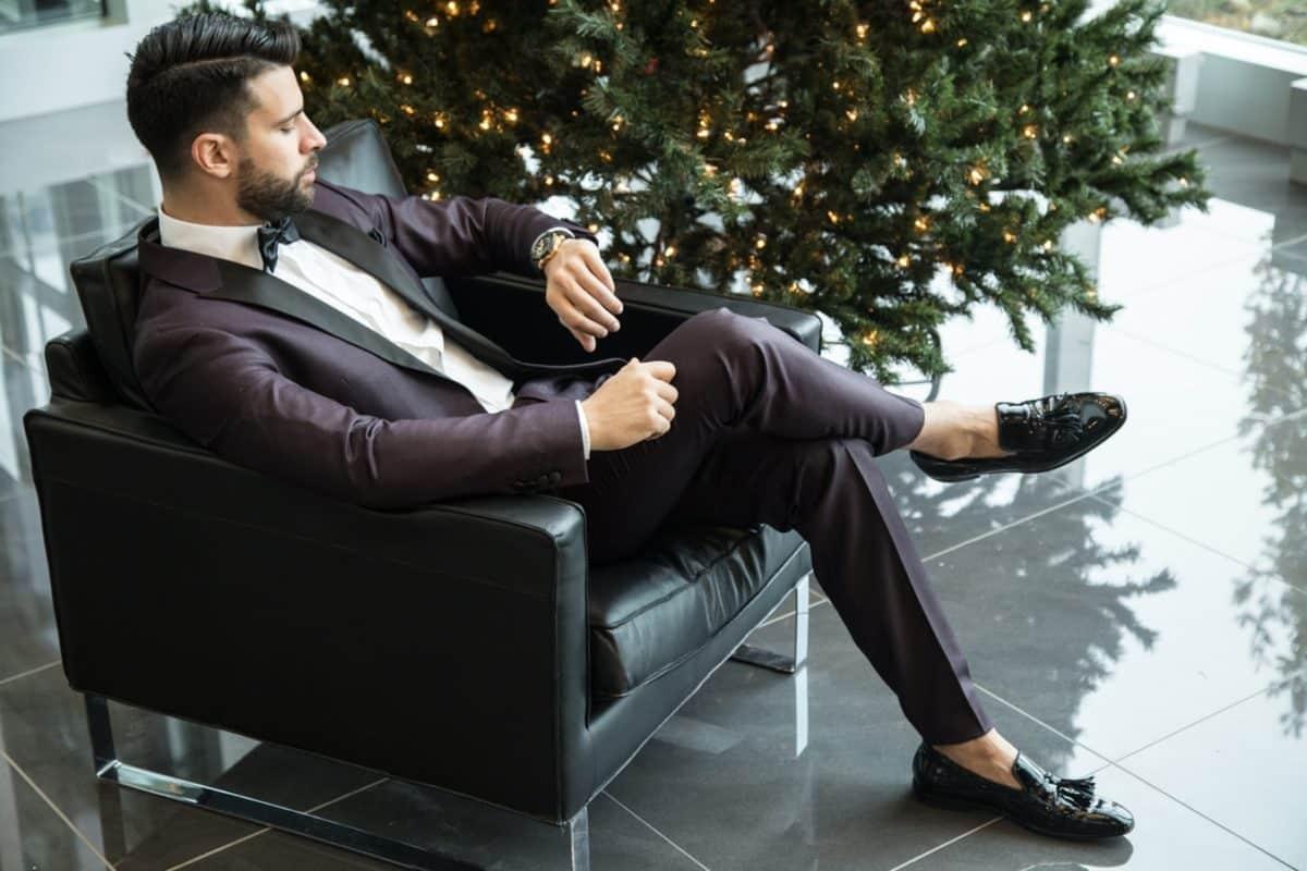 Мужчина сидит на диване и смотрит на часы
