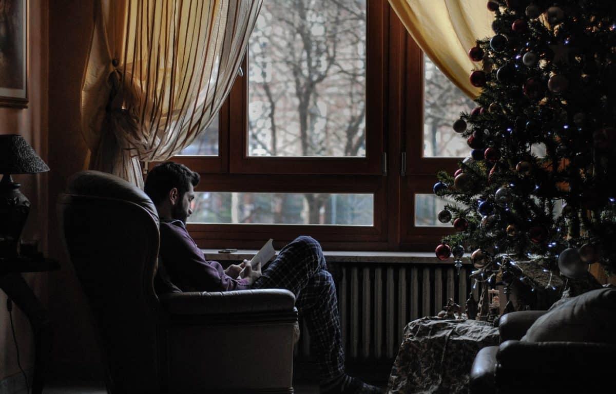 Мужчина сидит на кресле рядом с Новогодней елкой