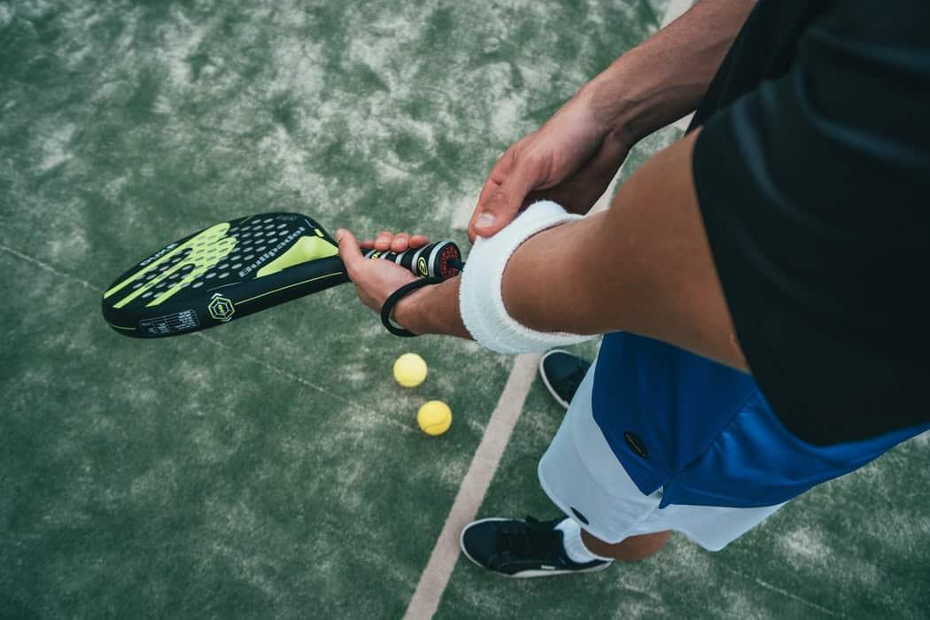Мужчина держит теннисную ракетку
