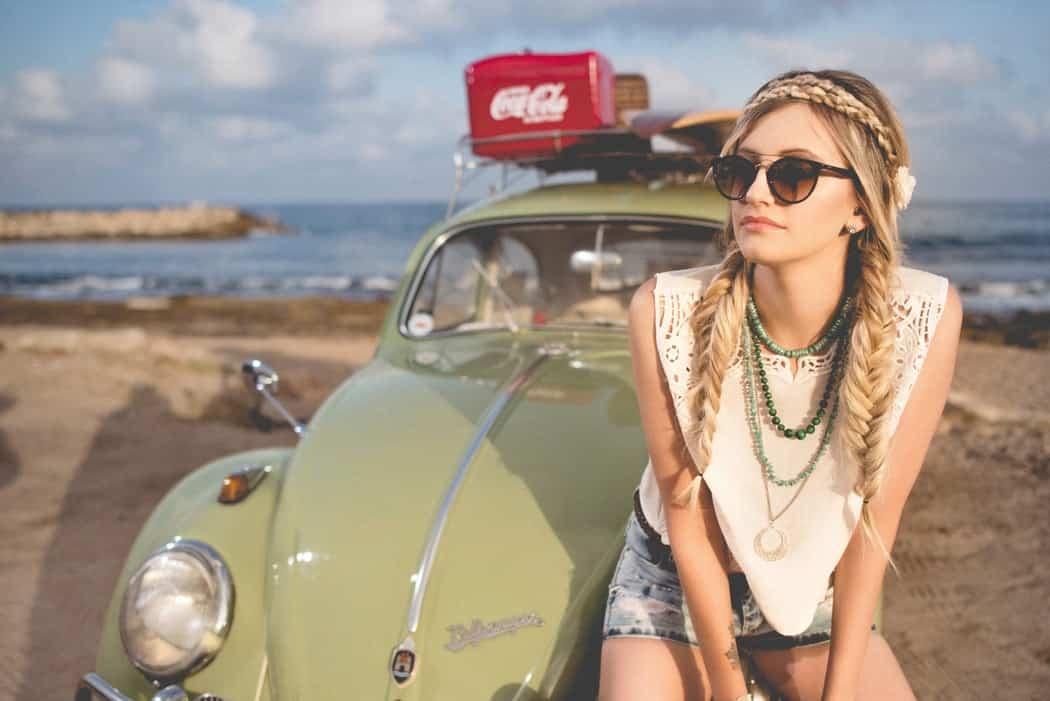 Женщина сидит на Volkswagen Beetle, припаркованном на берегу моря