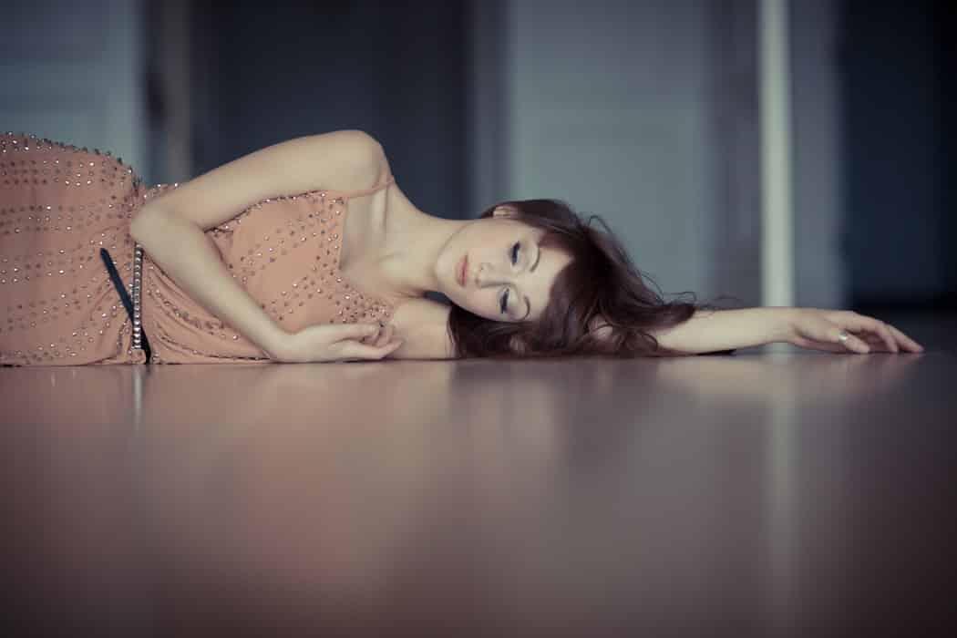 Девушка в розовом платье лежит на полу