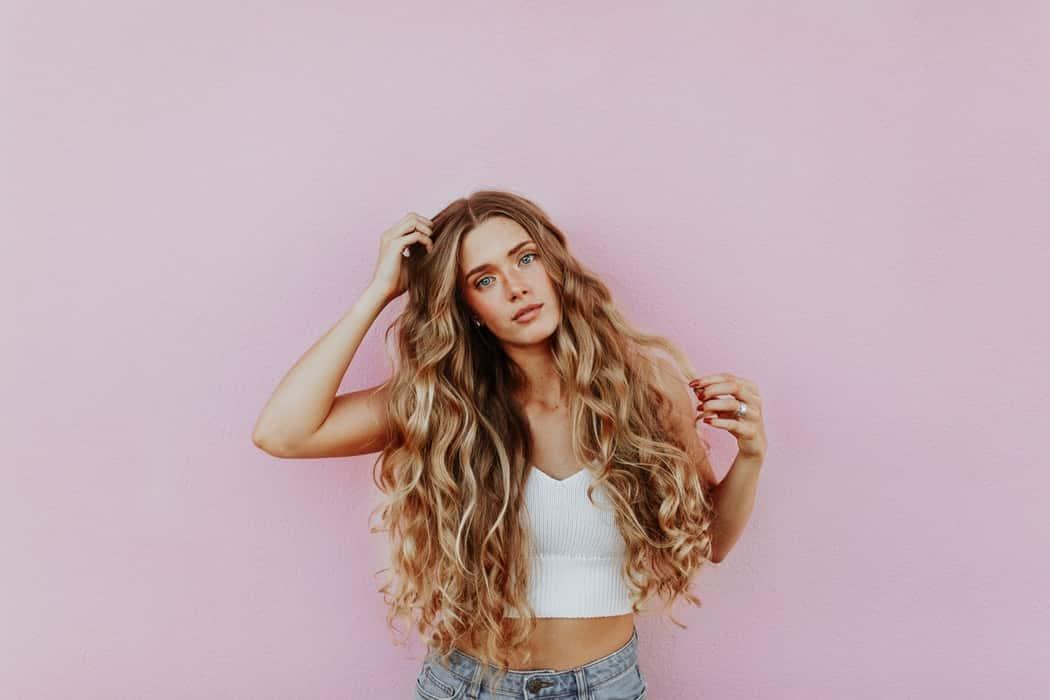 Девушка с длинными волосами на розовом фоне