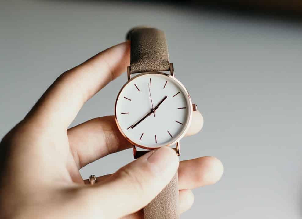 Человек держит аналоговые часы